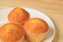 Close-up of Three Madeleine Cupcakes on White Plate Served on Wooden Table Royalty Free Stock Photo