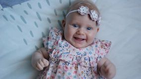 Three Months Old Baby Girl With Blue Eyes. Newborn Child, Little Adorable Peaceful and Attentive Girl Looking Surprised Smiling at. Close-up of a Three Months stock footage