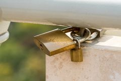 Close up of three padlocks attached to a steel railing on white marble and green background. Stock Photos