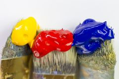 Macro three paint brushes with red, yellow and blue paint on a white background. Place for text, for banner, for site. Close-up of three paint brushes with red Stock Photos