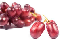 Close up of three pieces of red grape against a bunch at the background Stock Photography