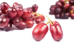 Close up of three pieces of red grape against a bunch at the background Royalty Free Stock Photo