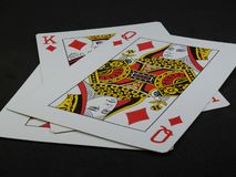 Three playing cards. We can see the King and the Queen of Diamonds. Close-up of three playing cards on a black surface. We can see the King and the Queen of stock photo