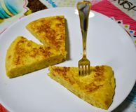 close up of three portions of a spanish omelet on a white plate on the tablecloth of a table. One portion of omelet has fixed a stock image