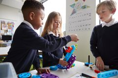 Close up of three primary school children working together with toy construction blocks in a classroom, side view royalty free stock images