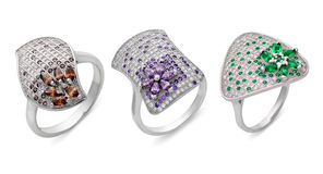 Close-up on three silver rings of different shapes. Three silver rings of different shapes with multi-colored precious stones on a white background stock illustration