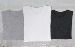 Close-up of the three t-shirts (black, white and grey). Stock Images