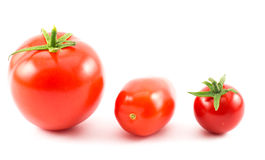 Close up of three tomatoes - big red, long and cherry on a white background.  royalty free stock images