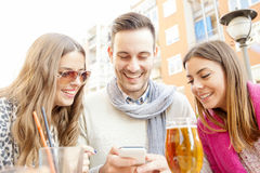 Close-up of three young cheerful people drinking beer outdoors Royalty Free Stock Photography