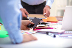 Close-up of three young creative designers working on project together. Team work Royalty Free Stock Image