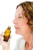Close-up of thughtful mature woman smelling medicine Stock Photo