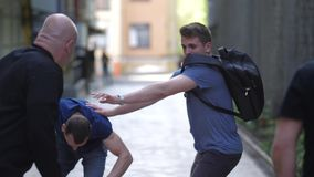 Male fighting with armed criminals on side street. Close-up of thugs attacking young man walking down deserted lane. Group of three muggers fighting with lonely stock footage