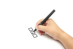 Close up of tick on middle of check list box. Businessman hand with pen on white background Stock Photo