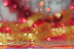 Tinsel in a foreground of colorful celebration lights. Close-up of tinsel in a foreground of colorful celebration lights royalty free stock photo