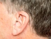 Close up of a tiny modern hearing aid behind ear. Macro close up of tiny modern hearing aid placed behind the ear of senior adult man Stock Photo