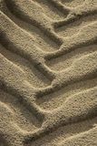 Close up of tire track in beach sand. Royalty Free Stock Photos