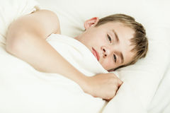Close up of tired boy in bed Royalty Free Stock Images