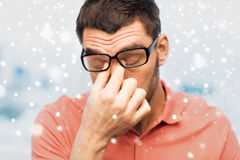 Close up of tired man in eyeglasses rubbing eyes. People, eyesight, stress, overwork and business concept - close up of tired man in eyeglasses rubbing his eyes royalty free stock photography