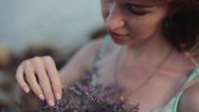 Close-up tiro do Lento-movimento Menina 'sexy' bonita com um ramalhete das flores no tempo ensolarado que sorri contra o mar video estoque