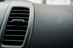 Close up to an air conditioner fan inside a modern car, black leather board of a modern car royalty free stock image