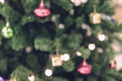 Close up to blurred Christmas tree decorated with lights and baubles. Royalty Free Stock Images