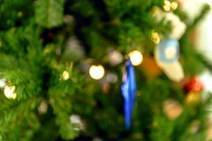 Close up to blurred Christmas tree decorated with lights and baubles. Stock Photography