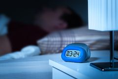 Close up to digital alarm clock on nightstand in bedroom. Man sleeping in bed in the background. Dreamy blur effect Stock Images
