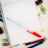 Close up to Empty lined page of notepad with blue pen above school or office supplies: pencils, clip, eraser. School and office theme background Royalty Free Stock Image