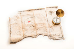Close up to gold nautical compass on old vintage map with fake island of Pirates treasure. Abstract island with pirates treasure chest Royalty Free Stock Photos