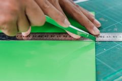 Close-up to hands of students are cutting  prints and stickers Royalty Free Stock Images