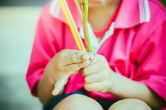 Close-up to kindergarten hands are tied with rubber for to make. Merit and candle light on Makha Bucha Day Royalty Free Stock Images