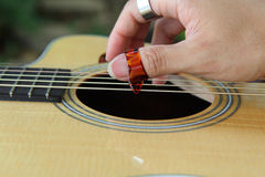 Close up to pick acoustic guitar Stock Photos
