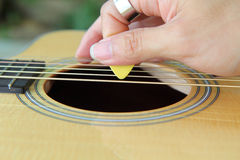 Close up to pick acoustic guitar Royalty Free Stock Images