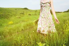 Close-up to the shoulders from below a young girl with a bouquet of wild flowers in her hand walks along a country road royalty free stock image