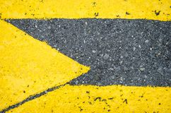 Close up to a yellow arrow in the direction to the right, close up to yellow pedestrian crossing with an arrow royalty free stock photo