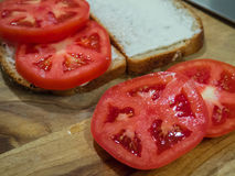 Close up Tomato Sandwich Slices. Making a tomato sandwich with slices of bread with mayonnaise on a cutting board with knife royalty free stock photography