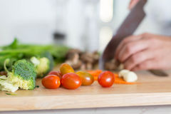 Close up of tomatoes, broccoli, carrots, and vegetables being cut on a wooden cutting board. Close up focused on cherry tomatoes Royalty Free Stock Image
