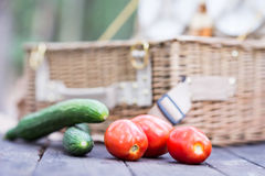 Close up of tomatoes and cucumbers over wooden table in front of an open picnic basket. Royalty Free Stock Photos