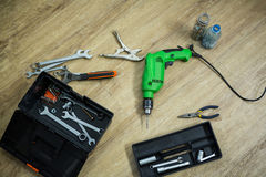 Close up of tool box and drill machine lying on floor. At home stock photos