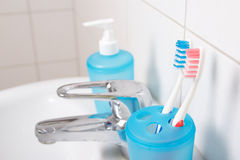 Close up of tooth brushes on white sink Royalty Free Stock Photography