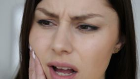 Close up of toothache gesture by young woman, face stock video footage