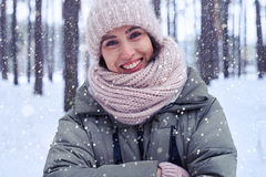 Close-up of toothy smiling model in the winter forest. Close-up of smiling woman wearing pink knitted cap and a scarf enjoying view in winter forest. Female is Royalty Free Stock Photos