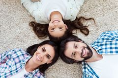 Close-up top above high angle view portrait of nice cute lovely friendly attractive kind cheerful cheery people mom dad. Lying on light carpet indoors royalty free stock photos