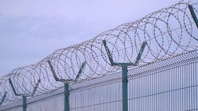 Close up of the top of the fence with barbed wire, prison