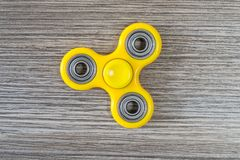 Close up top high angle above view photo of popular yellow fidget spinner, stress relieving toy against grey wooden background iso. Lated wooden gray background stock images
