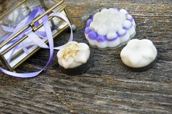 Close up, top shot of assorted organic, handmade, botanical flower shape soaps with lavender, purple ribbon in antique bowl on stock photo