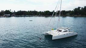Aerial View of a Anchored Catamaran Yacht Standing and people can Sunbathing on it`s Deck. stock video footage