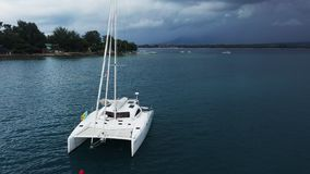 Aerial View of a Anchored Catamaran Yacht Standing and people can Sunbathing on it`s Deck. stock video