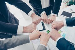 Close up top view cropped photo of experts in elegant classic outfit putting their fists together in a circle standing in work pl. Ace, station, making ritual royalty free stock image