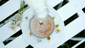 Close-up, top view, deceleration. On a white saucer, decorated with daisies, there is a glass, transparent cup with tea. Milk is poured into it. Dark brown tea stock video footage